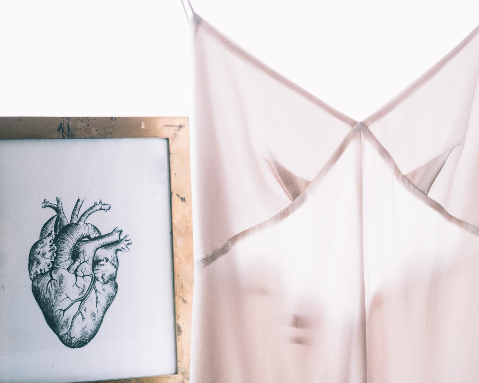 Illustration of heart in gold frame next to silk white wedding dress