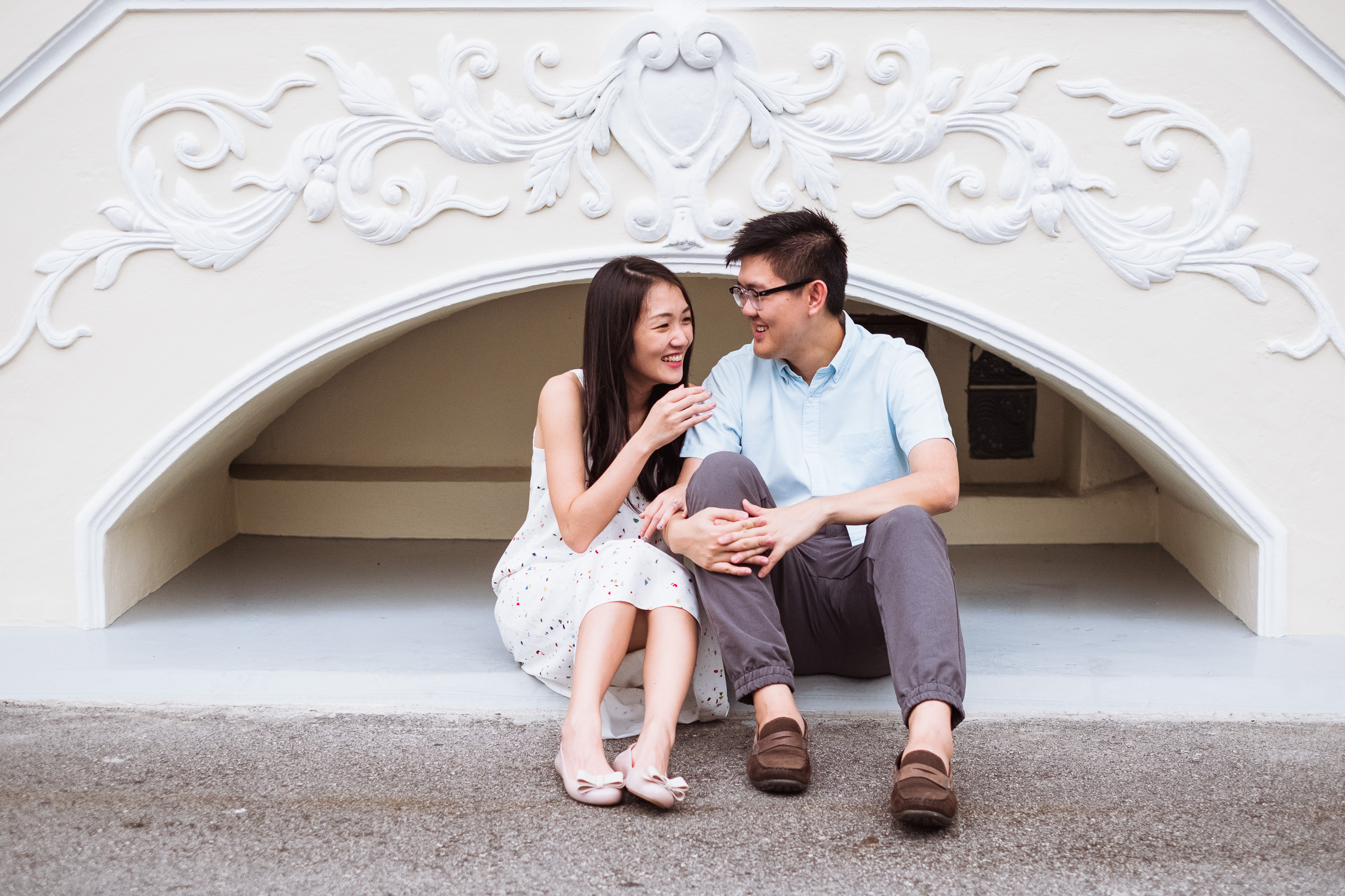 Laughing engaged couple in front of ornate wall of colourful traditional house, Singapore prewedding shoot