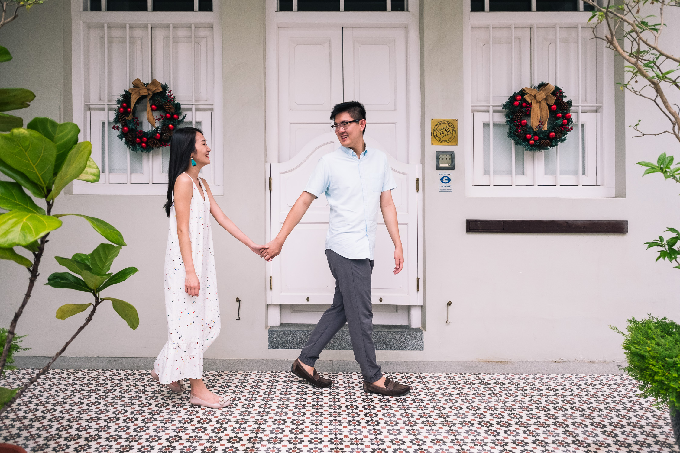 Tall Asian guy, girl in polka dot dress, Christmas wreaths, traditional houses in Singapore prewedding shoot
