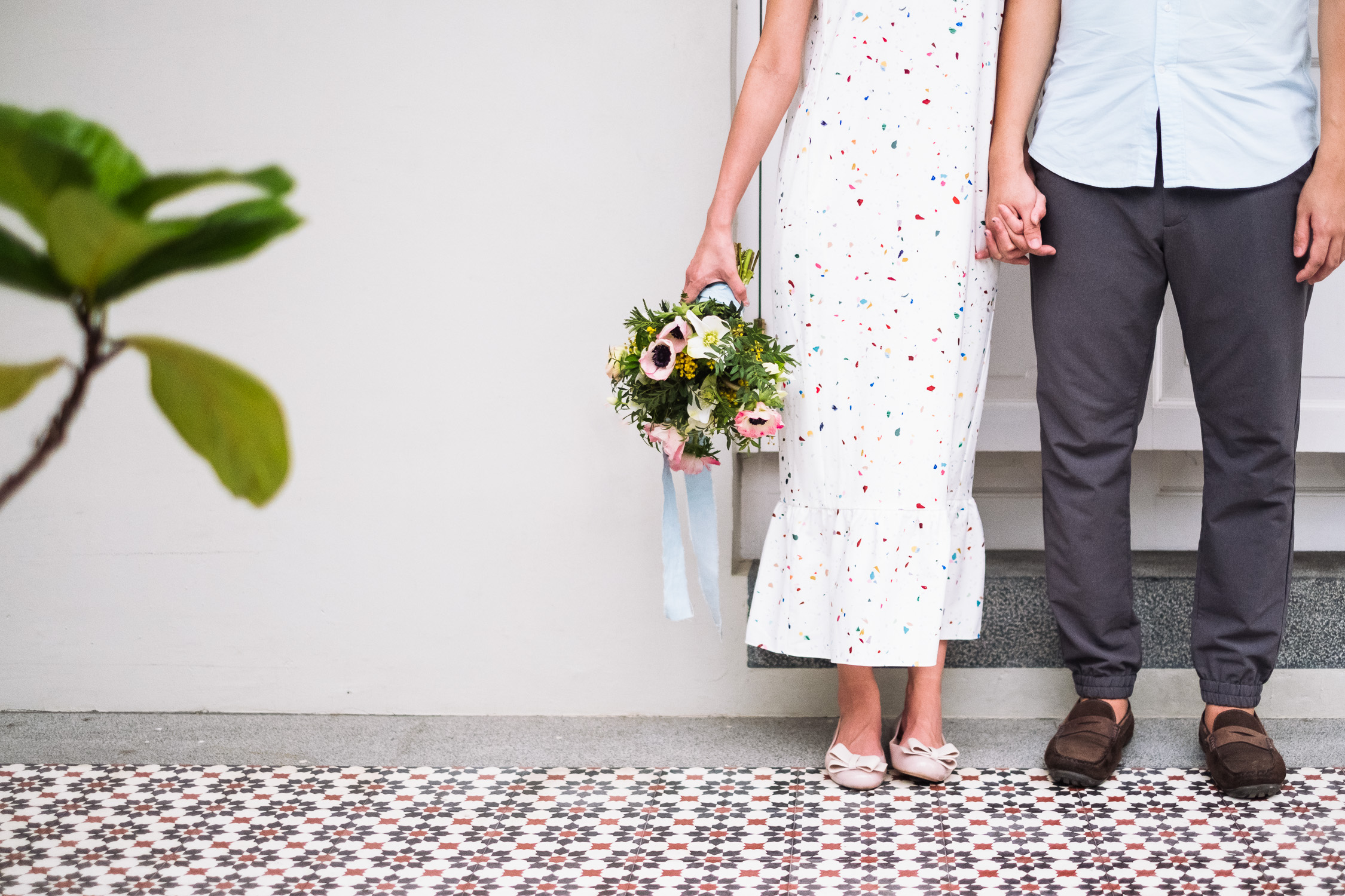 Engaged couple holding hands with bouquet and traditional tiled floors and fiddle leaf fig in Singapore prewedding shoot
