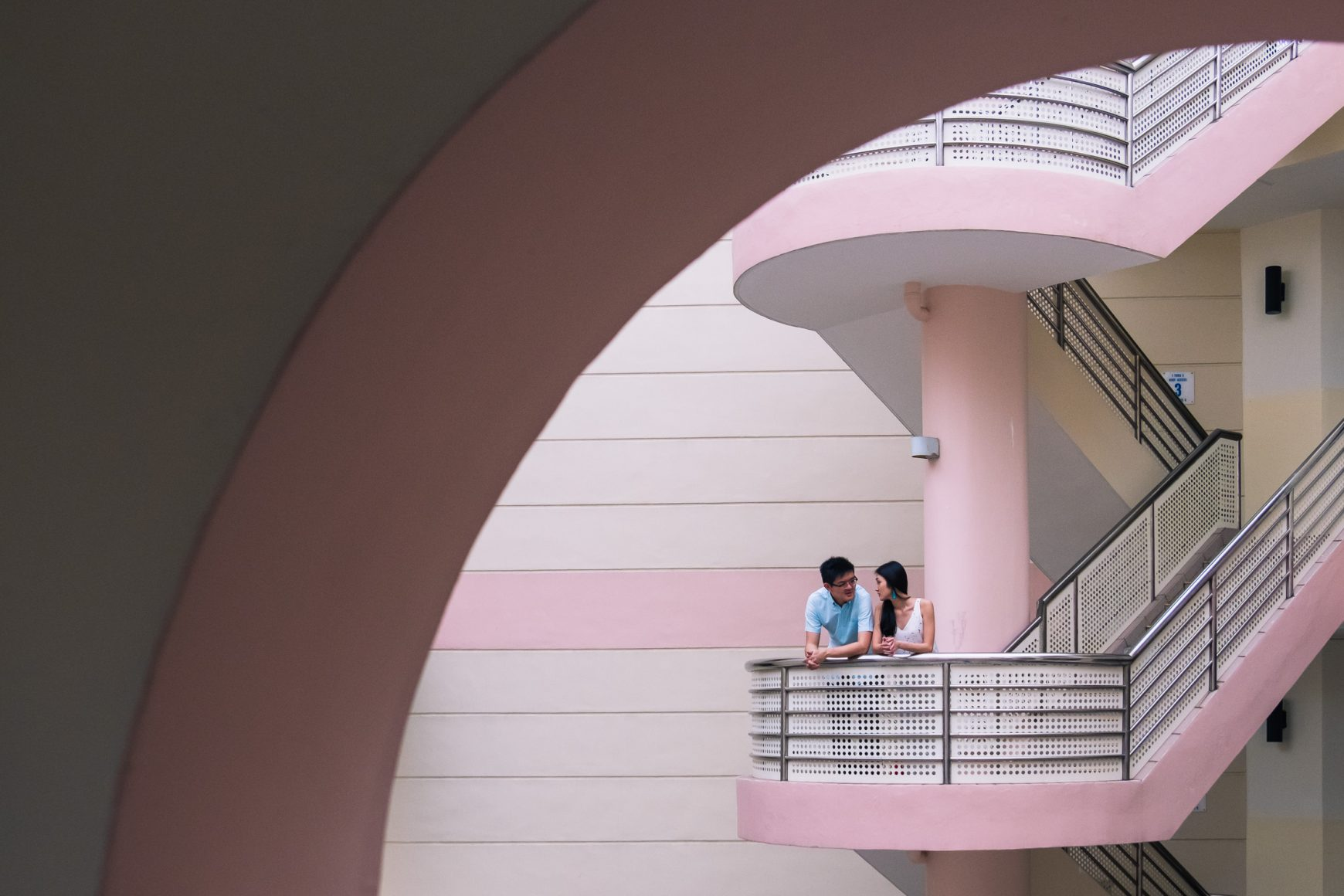 Engaged couple in circle frame, pink and white walls in Singapore community centre