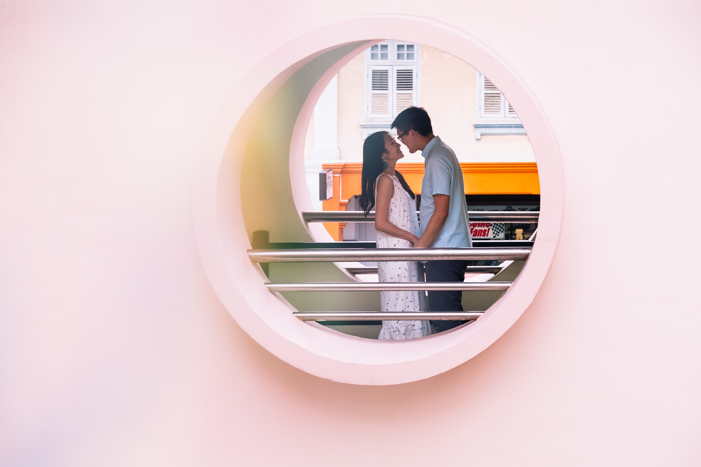Engaged couple in pink circle frame, in Singapore community centre
