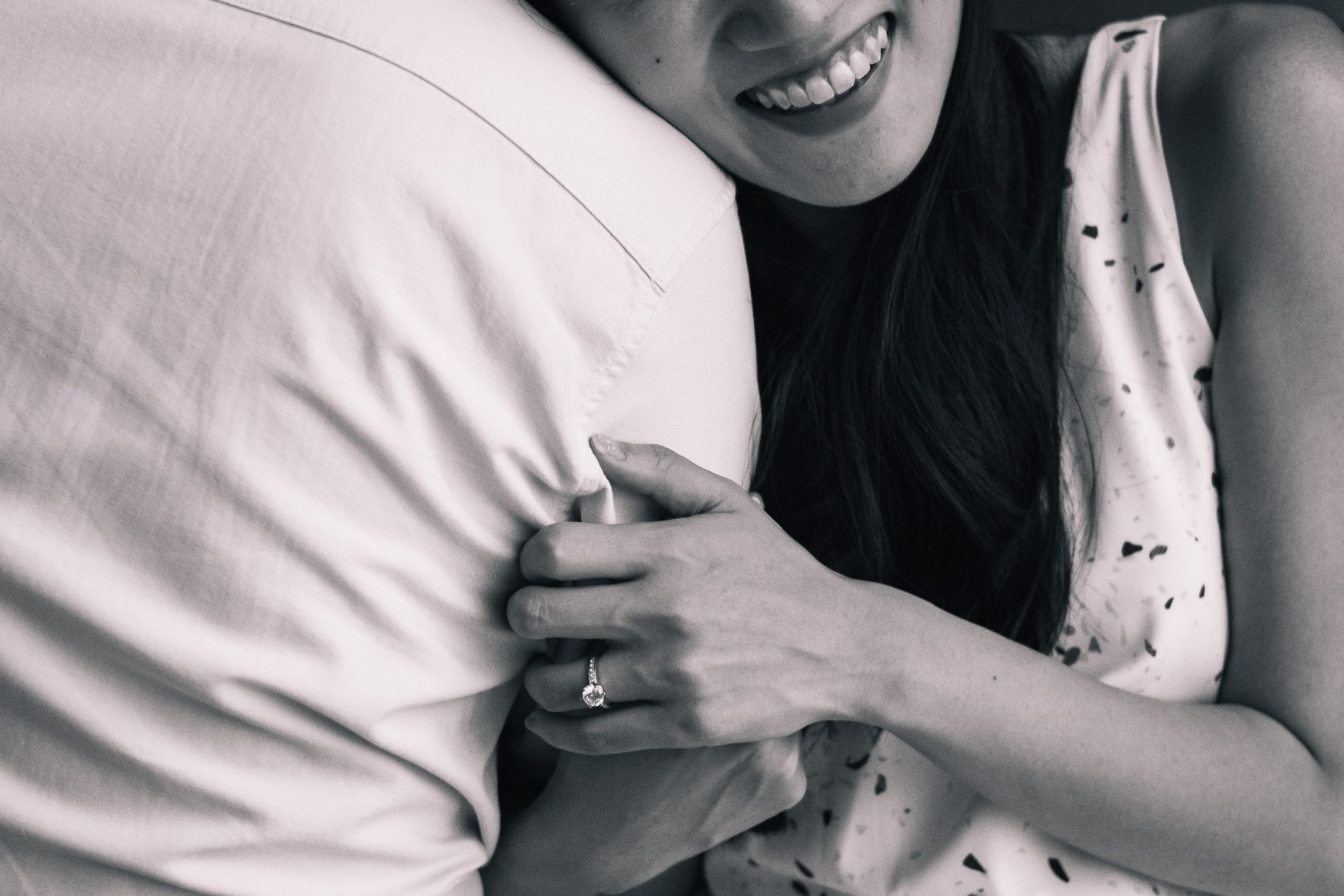 Smiling girl holding fiance arm with diamond ring at prewedding couple shoot