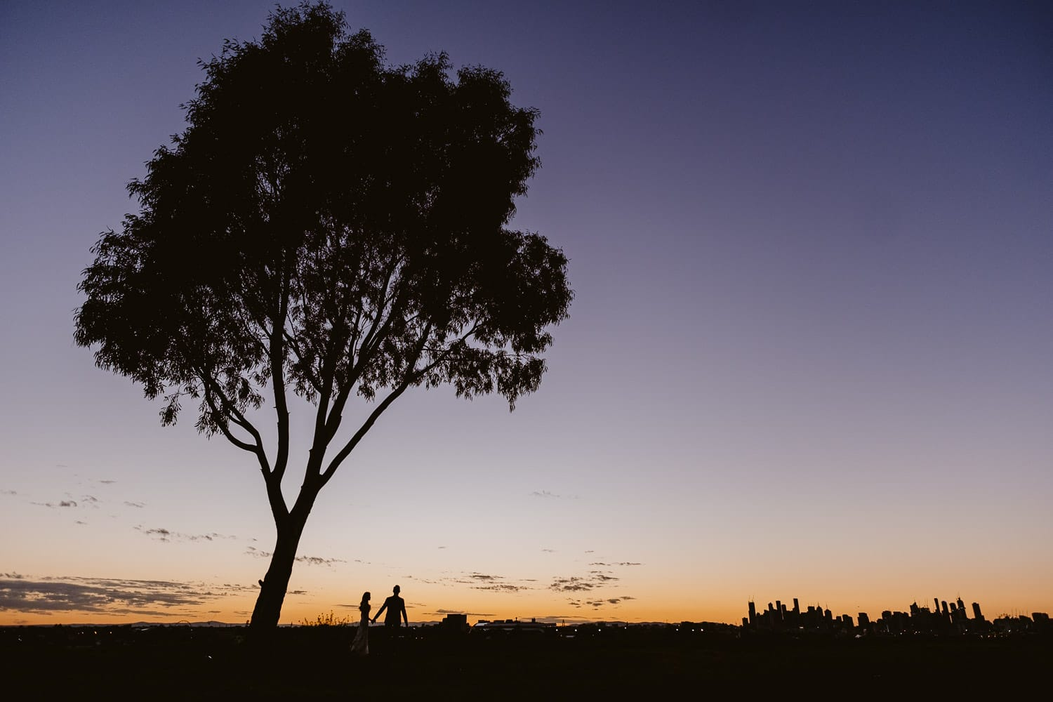 Silhouette of a couple looking at the sunrise with the Melbourne cityscape and a big tree in front them (Multi-day Overseas Prewedding Adventure in Melbourne)