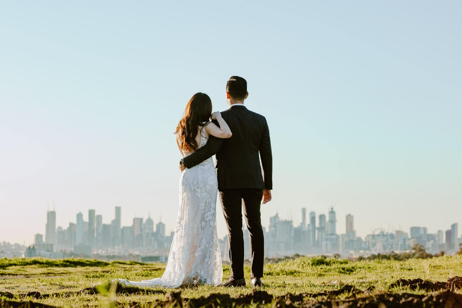 Asian couple look at the sunrise with the Melbourne cityscape and a blue sky in front of them (Multi-day Overseas Prewedding Adventure in Melbourne)