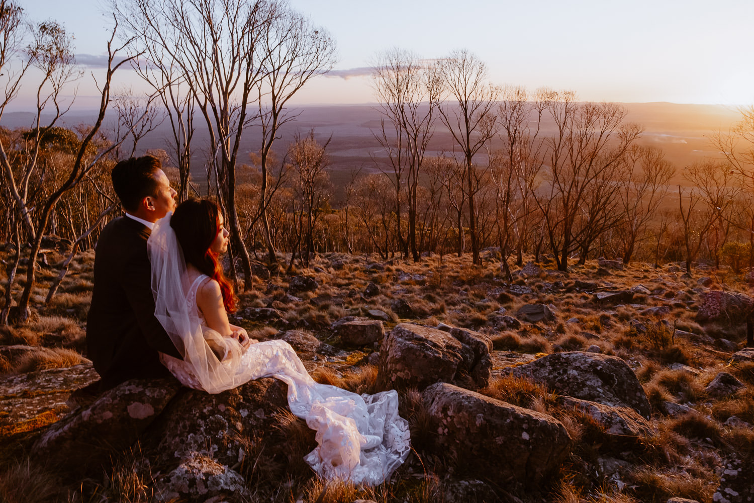 Engaged couple in wedding dress and wedding suit watches the sunset over the Macedon Ranges in Melbourne (Multi-day Overseas Prewedding Adventure in Melbourne)