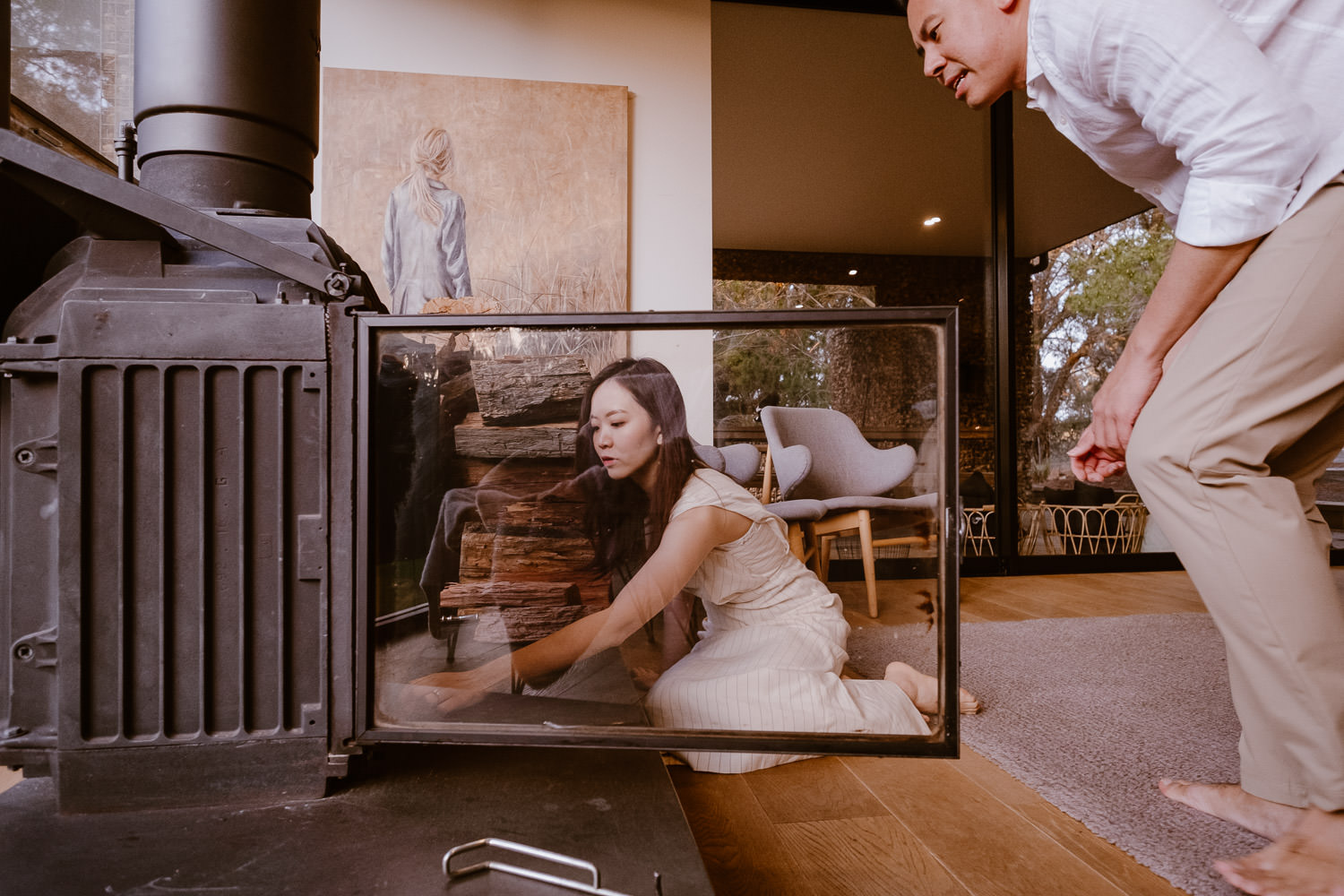 Engaged couple lighting a fire in the fireplace (Multi-day Overseas Prewedding Adventure in Melbourne)