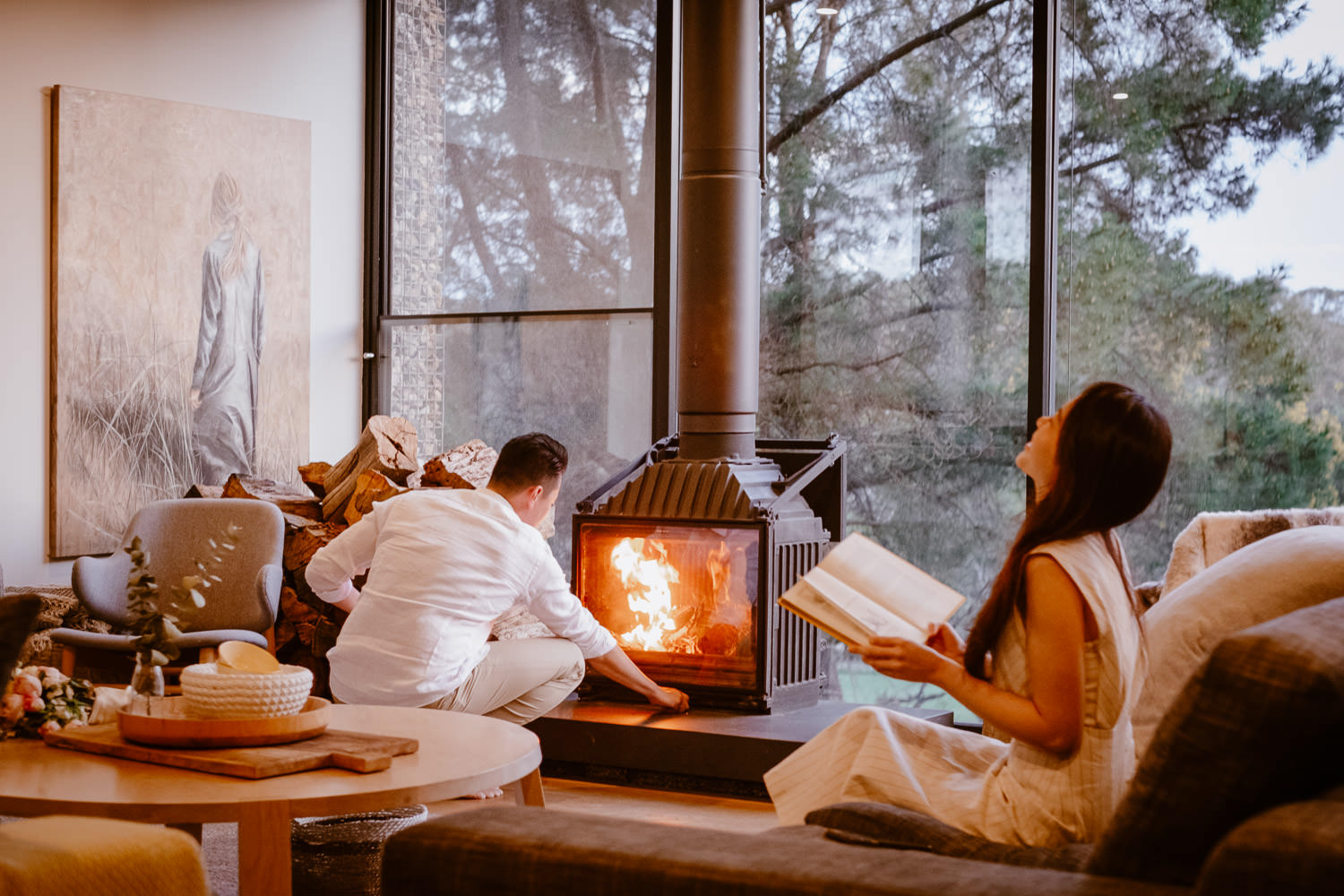 Guy lights a fire in the fireplace while the girl reads a book (Multi-day Overseas Prewedding Adventure in Melbourne)